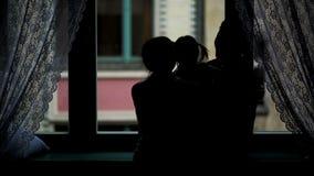 Opinión trasera la familia feliz que abraza cerca de la ventana Silueta de la madre, del padre y de su pequeña hija con dos