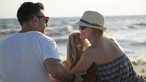 Opinión trasera la familia feliz que se sienta en la playa y que abraza gozando de Sunny Day During Summer Vacation caliente