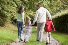 Opinión trasera la familia que recorre a lo largo de pista Fotos de archivo