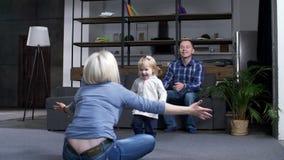 Opinión trasera la mamá que pide el niño que aprende caminar almacen de video