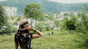 Opinión trasera la muchacha asombrosa en sombrero y vestido del verano en fondo del campo La mujer vuelve y mira la cámara almacen de video