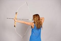 Opinión trasera la muchacha con el arco y la flecha Fotografía de archivo