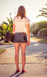 Opinión trasera la muchacha con un monopatín al aire libre el verano Imagenes de archivo
