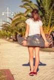 Opinión trasera la muchacha con un monopatín al aire libre encendido Fotografía de archivo libre de regalías