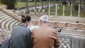 Opinión trasera la muchacha europea joven y el hombre mayor que se sientan y que hablan en las ruinas viejas del anfiteatro antig almacen de video