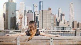 Opinión trasera la muchacha feliz con el pelo largo que disfruta de la opinión hermosa del horizonte de Manhattan en Nueva York q metrajes