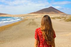 Opinión trasera la muchacha hermosa en la situación roja en la playa, EL Medano, Tenerife del vestido fotografía de archivo libre de regalías