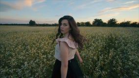 Opinión trasera la muchacha morena joven bonita con un pelo ondulado en paseos negros de la falda en un campo de flor Visi?n tras almacen de metraje de vídeo