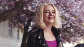 Opinión trasera la muchacha rubia joven atractiva que vaga en la ciudad floreciente de Sakura, vueltas a la cámara y sonrisas almacen de metraje de vídeo