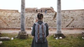 Opinión trasera la muchacha turística hermosa con la mochila que se coloca delante de pilares antiguos del anfiteatro en Ostia, I metrajes