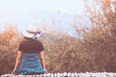 Opinión trasera la mujer asiática sola que lleva una sentada del sombrero Imagen de archivo libre de regalías