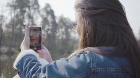 Opinión trasera la mujer bonita del encanto en la chaqueta y los vidrios de los vaqueros que toman la foto de la naturaleza hermo metrajes