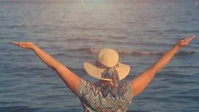 Opinión trasera la mujer con las manos para arriba sobre la opinión del mar en el tiempo de la puesta del sol almacen de metraje de vídeo