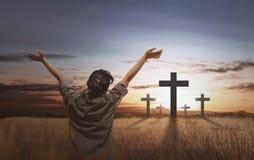 Opinión trasera la mujer con la palma y la cruz abiertas Foto de archivo