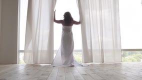Opinión trasera la mujer cubierta en el bedsheet que camina hacia la ventana del suelo al techo y que mira hacia fuera de detrás metrajes
