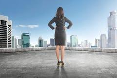 Opinión trasera la mujer de negocios asiática con la mano en su cintura en Foto de archivo
