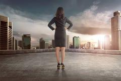 Opinión trasera la mujer de negocios asiática que mira la opinión de la puesta del sol Imagen de archivo