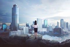 Opinión trasera la mujer de negocios asiática que se coloca de mirada de la ciudad Imágenes de archivo libres de regalías