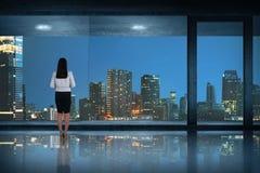 Opinión trasera la mujer de negocios asiática que se coloca de mirada de la ciudad Imagenes de archivo