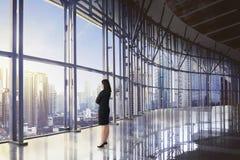 Opinión trasera la mujer de negocios asiática que se relaja mientras que mira skyscra Fotografía de archivo