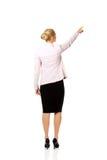 Opinión trasera la mujer de negocios joven que señala para somathing Imagen de archivo