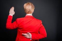 Opinión trasera la mujer de negocios que toma juramento falso Fotografía de archivo libre de regalías
