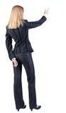 Opinión trasera la mujer de negocios rubia joven que señala en wal Foto de archivo