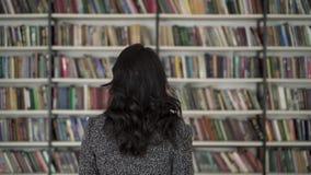 Opinión trasera la mujer del pelo negro que señala en un libro en un estante metrajes