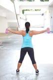 Opinión trasera la mujer deportiva que sostiene el barbell rosado con ambos brazos estirados hacia fuera Imágenes de archivo libres de regalías