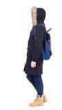 Opinión trasera la mujer en chaqueta del invierno con la mochila Imagenes de archivo