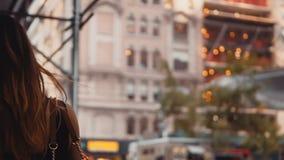 Opinión trasera la mujer hermosa joven que camina a través del centro de la ciudad de la construcción de edificios adentro de Nue almacen de video