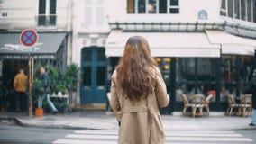 Opinión trasera la mujer hermosa joven que cruza el camino en París, Francia Hembra elegante en capa que camina en la calle metrajes