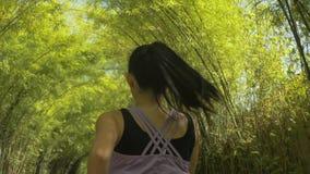 Opinión trasera la mujer joven con el funcionamiento de la cola de potro que practica activando entrenamiento en el parque hermos fotografía de archivo
