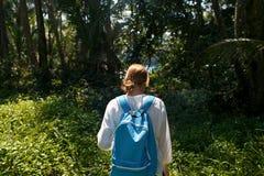 Opinión trasera la mujer joven con la mochila al aire libre que descubre la selva Fotografía de archivo libre de regalías
