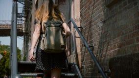 Opinión trasera la mujer joven con la mochila y el pelo largo que camina encima de las escaleras viejas del metal para incorporar almacen de video
