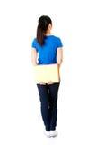 Opinión trasera la mujer joven del estudiante que sostiene un cuaderno. Fotografía de archivo