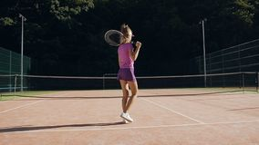 Opinión trasera la mujer joven en el uniforme del tenis que camina en la corte metrajes