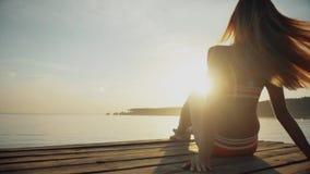 Opinión trasera la mujer joven en la playa que se relaja por el mar en verano almacen de video