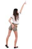 Opinión trasera la mujer joven hermosa en pantalones cortos que señala en la pared Imagen de archivo