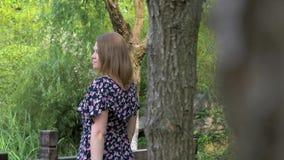 Opini?n trasera la mujer joven hermosa en vestido en parque de la ciudad del verano metrajes