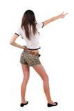 Opinión trasera la mujer joven hermosa que señala en la pared Foto de archivo libre de regalías