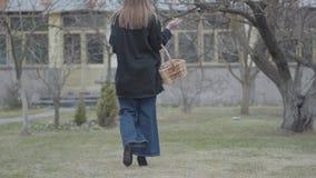 Opinión trasera la mujer joven que camina con la cesta de mimbre de nueces que sostienen el cepillo a disposición Artista atrac almacen de video