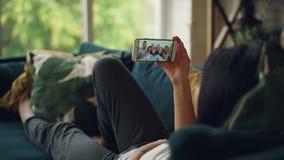 Opinión trasera la mujer joven que habla con los amigos en línea con el smartphone que mira la pantalla y que habla asistir en el almacen de video
