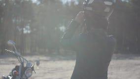 Opinión trasera la mujer joven que pone en la situación del casco de la motocicleta en su nueva moto en luz suave man?a metrajes