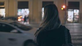 Opinión trasera la mujer morena joven que se coloca cerca del camino del tráfico y que mira alrededor por la tarde almacen de metraje de vídeo
