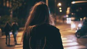 Opinión trasera la mujer morena que camina tarde en la noche en Roma, Italia Cruz de la muchacha el camino en el paso de peatones almacen de metraje de vídeo