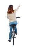 Opinión trasera la mujer punteaguda con una bicicleta Imágenes de archivo libres de regalías