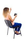 Opinión trasera la mujer punteaguda que se sienta en silla y miradas en el sc Fotografía de archivo