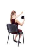 Opinión trasera la mujer punteaguda que se sienta en silla y miradas en el sc Fotografía de archivo libre de regalías