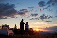 Opinión trasera la mujer que abraza acampar cercano del niño en montañas en el amanecer que se coloca en hierba con los wildflowe Imágenes de archivo libres de regalías